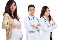Zwangere Aziatische vrouw die zich voor haar arts bevinden royalty-vrije stock foto