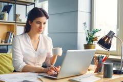 Zwangere bedrijfsvrouw die bij de zitting van het bureaumoederschap het doorbladeren laptop het drinken koffie werken stock fotografie
