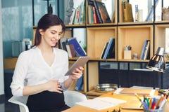 Zwangere bedrijfsvrouw die bij de zitting werken die van het bureaumoederschap digitale tablet houden royalty-vrije stock fotografie