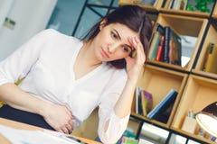 Zwangere bedrijfsvrouw die bij vermoeide de zitting werken van het bureaumoederschap stock afbeelding