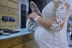 Zwangere bruid in huwelijkskleding dichtbij lijst royalty-vrije stock fotografie