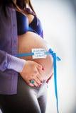 Zwangere buik die tegen witte achtergrond wordt geïsoleerd Stock Foto's