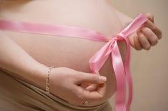 Zwangere buik met roze lint royalty-vrije stock foto's