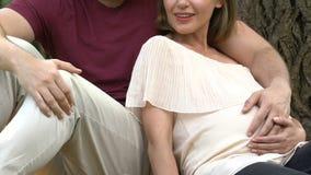 Zwangere dame en echtgenoot die, over toekomstige baby, familie dromen in openlucht liggen die stock footage
