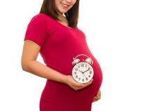 Zwangere de muurklok van de vrouwenholding Zijn tijd Royalty-vrije Stock Afbeeldingen
