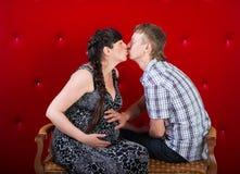 Zwangere donkerbruine vrouw met echtgenoot op rode achtergrond Paar Royalty-vrije Stock Foto's