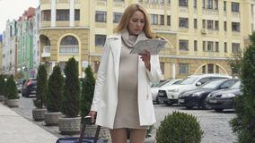 Zwangere elegante dame die met koffer hotel met kaart zoeken, zakenreis stock video