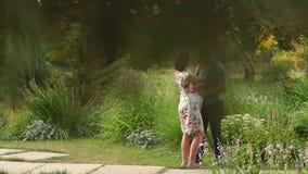 Zwangere en haar echtgenootgang in het park van de de zomerzon stock videobeelden
