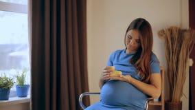 Zwangere gelukkige de babyschoenen van de vrouwenholding in haar handen Mamma die haar Baby verwachten Zwangere vrouwenbuik Zwang stock video