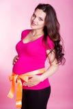 Zwangere gelukkige vrouw met lint op buik Stock Afbeeldingen