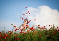 Zwangere gelukkige vrouw op een bloeiend papavergebied Stock Afbeelding