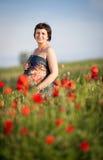Zwangere gelukkige vrouw op een bloeiend papavergebied Stock Fotografie