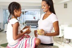 Zwangere Moeder en Dochter die Juice In Kitchen drinken royalty-vrije stock foto's
