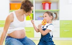 Zwangere moeder en dochter met lollys stock afbeeldingen