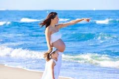 Zwangere moeder en dochter op het strand Stock Afbeeldingen