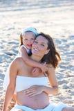 Zwangere moeder en dochter op het strand stock afbeelding