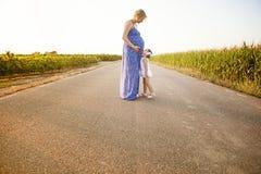 Zwangere moeder en haar dochter tussen cornfields Stock Foto's