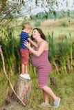 Zwangere moeder en haar zoon die samen spelen stock afbeeldingen