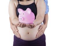 Zwangere moeder en moneybox Stock Foto's