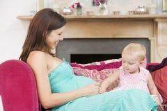 Zwangere moeder met dochter in woonkamer stock foto