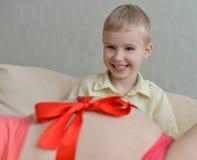 Zwangere moeder met haar leuke kleine jongen op de bank Royalty-vrije Stock Afbeelding