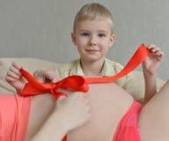Zwangere moeder met haar leuke kleine jongen op de bank Stock Afbeeldingen