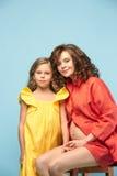 Zwangere moeder met tienerdochter Het portret van de familiestudio over blauwe achtergrond stock afbeelding