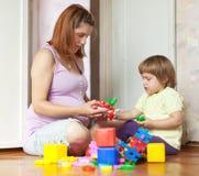 Zwangere moederspelen met kind Stock Fotografie
