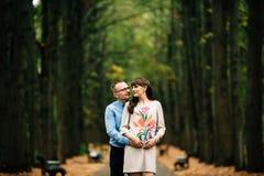 Zwangere mooie vrouw en haar het knappe echtgenoot mooie koesteren in de herfstpark Royalty-vrije Stock Afbeelding