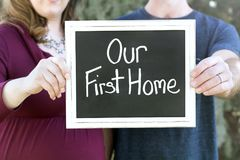 Zwangere nieuwe familie die hun nieuw huis kopen die ons eerste huisteken houden royalty-vrije stock foto
