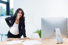 zwangere onderneemster met rugpijn bij werkplaats het kijken stock afbeelding