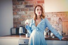 Zwangere vrouw in blauwe kleding met kop van koffie of thee stock afbeeldingen