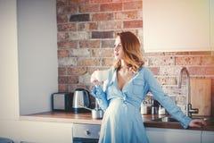 Zwangere vrouw in blauwe kleding met kop van koffie of thee stock foto