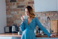 Zwangere vrouw in blauwe kleren met kop thee of koffie royalty-vrije stock fotografie