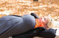 Zwangere vrouw in de herfstpark Stock Foto's