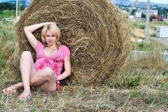 Zwangere vrouw dichtbij hooiberg Stock Afbeeldingen