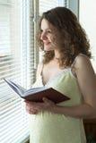 Zwangere vrouw dichtbij venster Royalty-vrije Stock Afbeelding