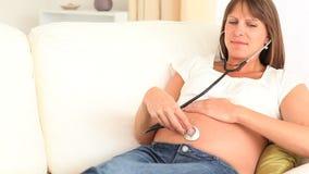 Zwangere vrouw die aan haar buik luisteren stock video