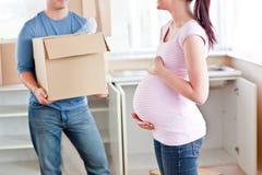 Zwangere vrouw die aan haar doos van de echtgenootholding spreekt Royalty-vrije Stock Foto's