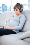 Zwangere vrouw die aan muziek luisteren terwijl het zitten in woonkamer Stock Foto