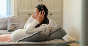Zwangere vrouw die aan muziek op hoofdtelefoons in woonkamer 4k luisteren stock footage