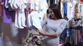 Zwangere vrouw die Babykleding in baby en moederschapswinkel kiezen stock footage