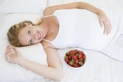 Zwangere vrouw die in bed met kom fruit ligt royalty-vrije stock foto's