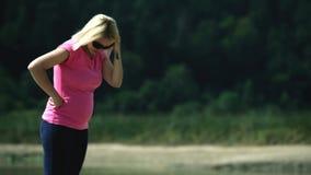 Zwangere vrouw die de vloer onderzoeken en de barsten met haar vingers drukken stock footage
