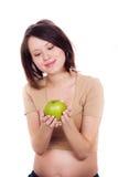 Zwangere vrouw die een appel in haar handen houdt Royalty-vrije Stock Foto