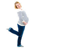 Zwangere vrouw die en haar buik glimlachen houden Stock Afbeeldingen