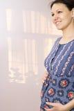 Zwangere vrouw die en zich op maag bevindt houdt Royalty-vrije Stock Afbeelding