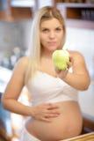 Zwangere vrouw die groen Apple en het glimlachen houden Stock Afbeeldingen