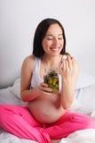 Zwangere vrouw die groenten in het zuur eet stock foto's