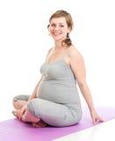 Zwangere vrouw die gymnastiek- geïsoleerdeo oefeningen doen stock afbeelding